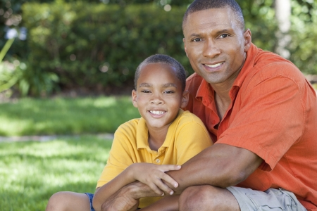 A happy African American man and boy, father and son, family together outside in summer sunshine Banco de Imagens