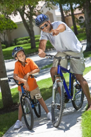 An African American man and boy child, father & son riding bicycles in the summer.
