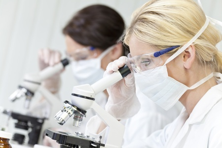 medical research: A blond female medical or scientific researcher or doctor using her microscope in a laboratory with her colleague out of focus behind her. Stock Photo