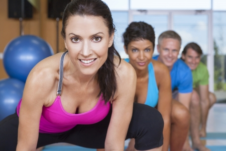 An interracial group of middle aged people, men and women, practicing yoga at a gym