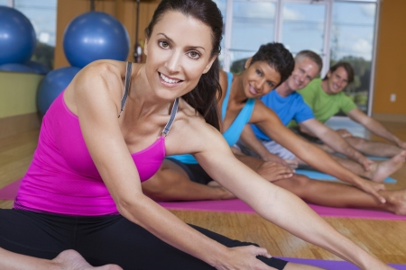 middle aged men: An interracial group of middle aged people, men and women, practicing yoga at a gym
