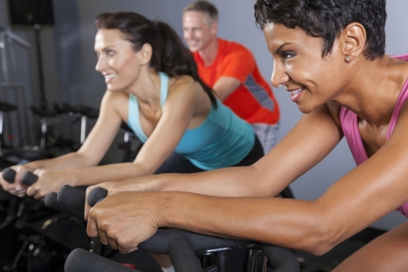 An African American woman and middle aged friends on spinning exercise bikes at a gym photo