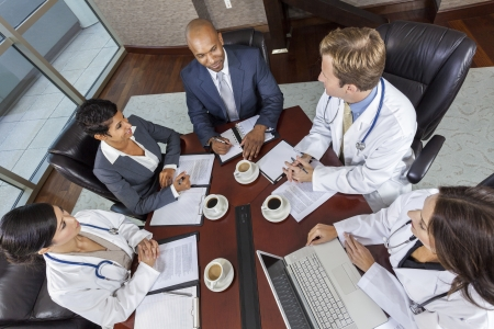 Interracial group of business men   women, businessmen and businesswomen and doctors team meeting in hospital boardroom photo