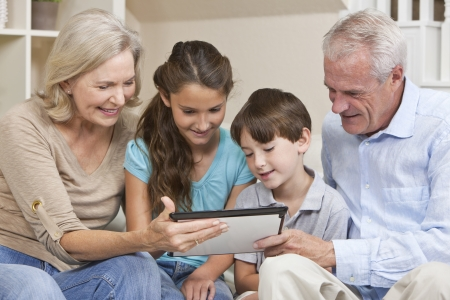 old pc: Senior adults and children, grandparents   grandchildren, sitting on a sofa at home having fun using a tablet computer