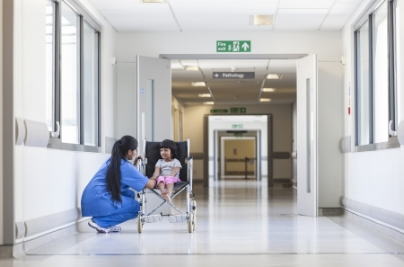 Young female child patient in wheelchair sitting in hospital corridor with Indian Asian female nurse Foto de archivo