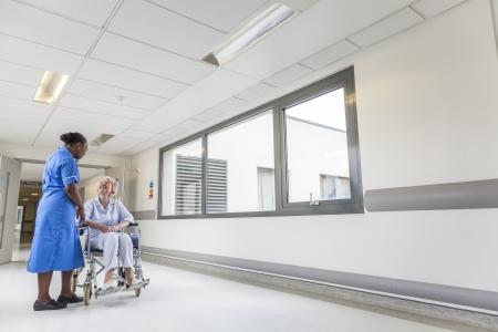 휠체어는 아프리카 계 미국인 여성 간호사와 병원 복도에 앉아있는 수석 여성 여자 환자 스톡 콘텐츠