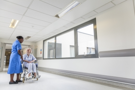 Senior female woman patient in wheelchair sitting in hospital corridor with African American female nurse Stock Photo