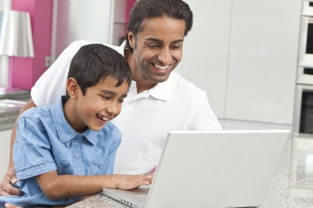 pakistani: Asian Indian father and son, man and boy, using laptop computer in the kitchen at home