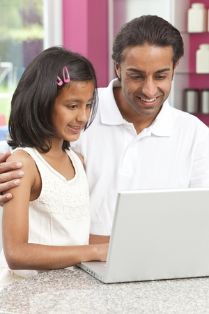 indian male: Asian Indian father and daughter, man and girl, using laptop computer in the kitchen at home Stock Photo