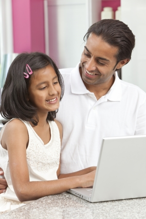 Asian Indian father and daughter, man and girl, using laptop computer in the kitchen at home photo