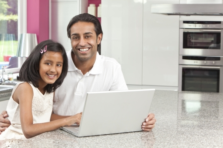 asian indian: Asian Indian father and daughter, man and girl, using laptop computer in the kitchen at home Stock Photo