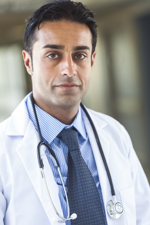 A male Asian Indian man doctor wearing white coat, shirt and tie with stethoscope, pictured in hospital Stock Photo