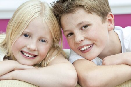 Happy young boy   girl children brother and sister on a sofa at home photo