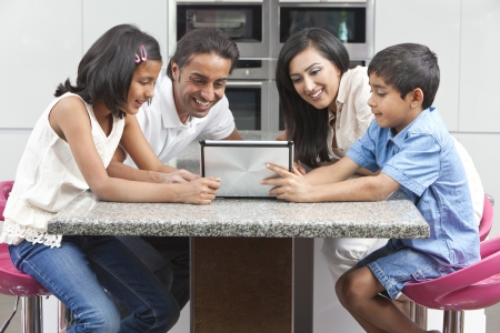 Aziatische Indische familie man vrouw, kinderen, meisje en jongen, die tabletcomputer in de keuken thuis Stockfoto