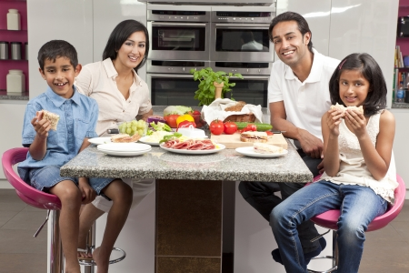 An attractive happy, smiling Asian Indian family of mother, father, son and daughter eating healthy food   salad in the kitchen at home
