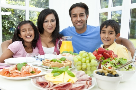 woman eat: An attractive happy, smiling Asian Indian family of mother, father, son and daughter eating healthy food   salad at a dining table  Stock Photo