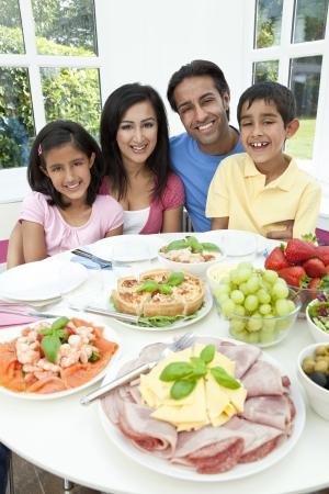 familia comiendo: Una atractiva sonriente feliz familia india, asiática de la madre, padre, hijo y su hija comiendo ensalada de alimentos saludables en una mesa de comedor