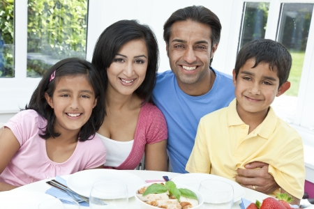 An attractive happy, smiling Asian Indian family of mother, father, son and daughter eating healthy food at a dining table