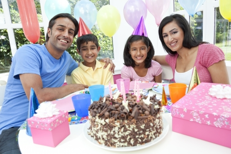 fiesta familiar: Familia asi�tica india, madre, padre, hijo, hija, celebrando una fiesta de cumplea�os con un pastel de chocolate
