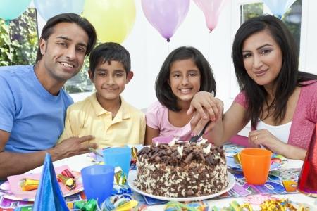 Aziatische Indische familie, moeder, vader, zoon, dochter vieren van een verjaardagsfeestje het snijden van de taart