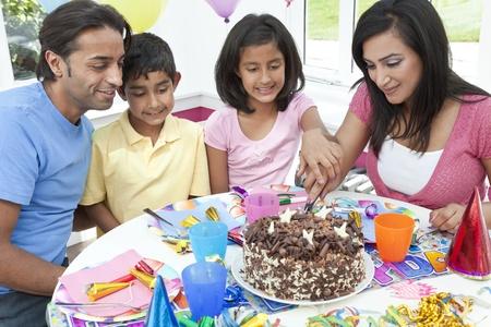 familia comiendo: Familia asi?tica india, madre, padre, hijo, hija, celebrando una fiesta de cumplea?os del corte de la torta