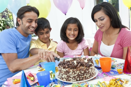 Asian Indian family, mother, father, son   daughter celebrating a birthday party cutting the cake