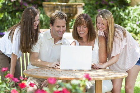 An attractive happy, smiling family of mother, father and two daughters sitting using a laptop computer outside in the garden in warm summer sunshine photo