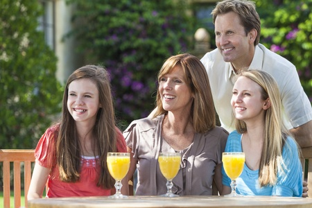 An attractive happy, smiling family of mother, father and two daughters drinking orange juice at a table outside  photo