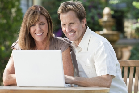 togther: Attractive, successful and happy middle aged man and woman couple in their thirties, sitting togther outside in a garden using a laptop computer