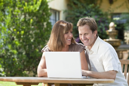togther: Attractive, successful and happy middle aged man and woman couple in their thirties, sitting togther outside in a garden using a laptop computer. Stock Photo