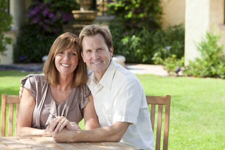 togther: Attractive, successful, happy middle aged man and woman maried couple in their thirties, sitting togther outside in a garden sitting at a table.
