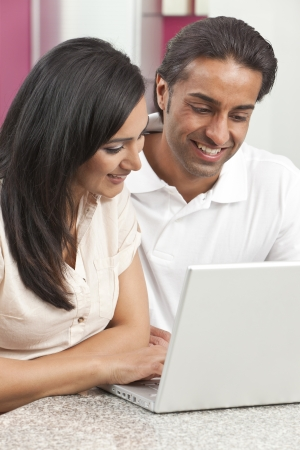 Asian Indian couple, husband & wife, man and woman, using laptop computer in the kitchen at home photo