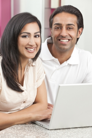 Asian Indian couple, husband & wife, man and woman, using laptop computer in the kitchen at home Foto de archivo