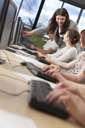 Teacher & group of male and female students using computers at a college Foto de archivo