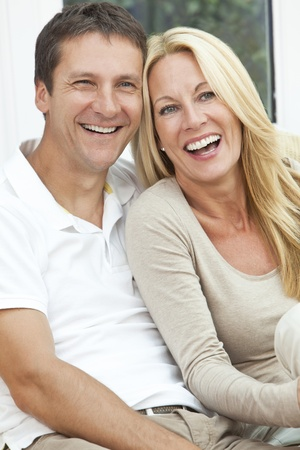 Portrait shot of an attractive, successful and happy middle aged man and woman couple in their forties, sitting together at home on a sofa, smiling and laughing Foto de archivo