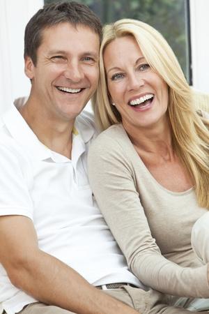 Portret shot van een aantrekkelijke, succesvolle en gelukkige man en vrouw paar in de veertig middelbare leeftijd, samen om thuis te zitten op een sofa, lachend en lachen