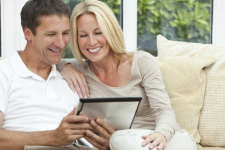 middle aged: Portrait shot of an attractive, successful and happy middle aged man and woman couple in their forties, sitting together at home on a sofa using tablet computer