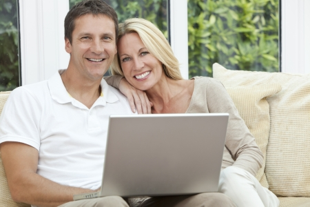 pareja en casa: Hombre envejecido medio atractivo, exitoso y feliz y joven mujer en sus cuarenta a�os, sentados juntos en el hogar en un sof� con ordenador port�til Foto de archivo