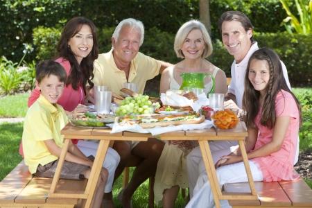 familia comiendo: Un atractivo familia feliz y sonriente de la madre, padre, abuelos, hijo y su hija comer alimentos saludables en una mesa de picnic al aire libre Foto de archivo