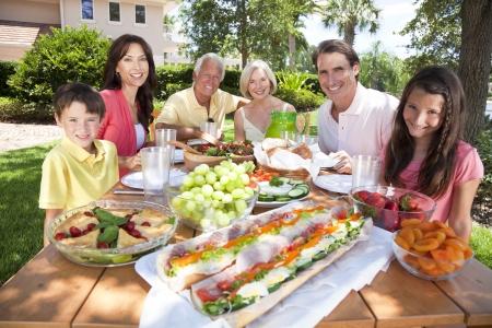 Een aantrekkelijke gelukkig, glimlachen familie van moeder, vader, grootouders, zoon en dochter gezond eten op een picknicktafel buiten