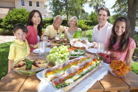 어머니, 아버지, 할아버지, 할머니, 아들과 딸의 매력적인 미소, 행복 가족은 외부 피크닉 테이블에 건강한 음식을 먹고