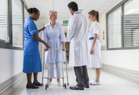 Senior vrouwelijke vrouw ziekenhuispatiënt in de gang met twee vrouwelijke verpleegkundigen, een Afro-Amerikaanse en Aziatische mannelijke arts.