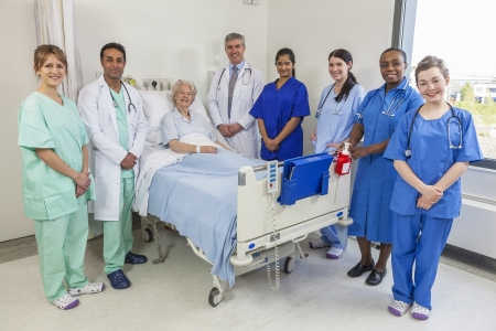 Senior female woman patient in hospital bed surrounded by the multi ethnic interracial medical team of men and women male and female doctors and nurses