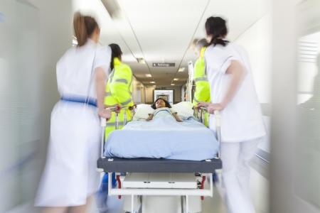 paciente en camilla: Una moci�n borrosa foto de un indio paciente del ni�o joven asi�tica en camilla camilla o ser empujado a la velocidad a trav�s de un pasillo del hospital por los m�dicos y enfermeras de la sala de emergencias