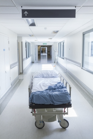 Bereavement, death or loss concept shot of empty bed, gurney or stretcher with drip in hospital corridor