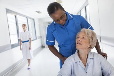 휠체어에 수석 여성 여자 환자는 아프리카 계 미국인 여성 간호사와 병원 복도 아래로 밀려