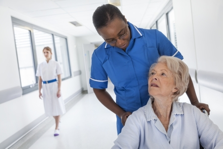 Senior female woman patient in wheelchair being pushed down hospital corridor with African American female nurse