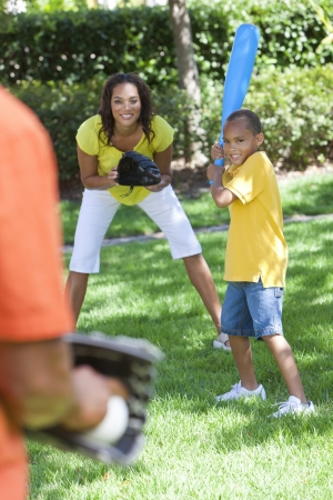 African American family, man, woman, boy child, mother, father, son playing baseball together outside. Stok Fotoğraf
