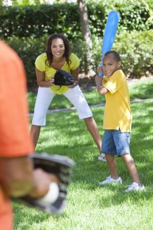 guante de beisbol: Familia afroamericana, hombre, mujer, ni�o ni�o, madre, padre, hijo jugando al b�isbol juntos fuera. Foto de archivo