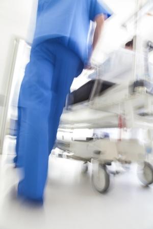 emergencia: Una moci�n borrosa foto de un paciente en camilla o cama camilla de ser empujado a la velocidad a trav�s de un pasillo del hospital por los m�dicos y enfermeras de la sala de emergencias